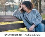 sad black woman seated alone on ... | Shutterstock . vector #716862727
