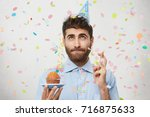 Small photo of Pleasant looking male with stubble, holds cupcake, keeps fingers crossed, going to make wish and blow out candle on cupcake, celebrates natal day, stands over white wall with colorful confetti