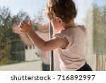 little child by the window | Shutterstock . vector #716892997