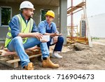 two workers wearing protective... | Shutterstock . vector #716904673