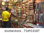 Small photo of Riyadh, Saudi Arabia - circa 2015: An expat looks for an item at a souvenir shop or Arabic souk in Dirah disctrict where price is set through bargaining
