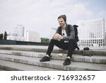 Small photo of The traveller is sitting on the steps after the long trip and holding the burger in his hands. He is so hungry that he can't wait to devour the lunch. The guy is tired but he looks happy