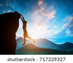 man hanging on the edge of... | Shutterstock . vector #717229327