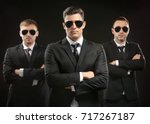 handsome bodyguards on dark... | Shutterstock . vector #717267187