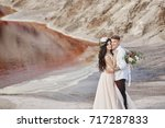 bride and groom walk along the... | Shutterstock . vector #717287833