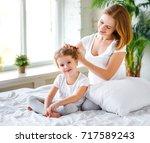 cute mother combing hair... | Shutterstock . vector #717589243