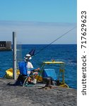man fishing on a harbor with... | Shutterstock . vector #717629623