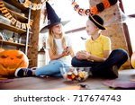 Small photo of Sweets for us! Treat or trick! Friendly small kids in carnival head wear, with colorful treats, near them carved pumpkins, fall leaves, they sit on the brown wooden floor, sharing the yummies