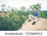 Small photo of A tourist sits and looks into the distance. Man sit. Wonderful mountain landscape.
