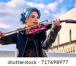 Small photo of Woman perform music on violin in park outdoor. Girl performing jazz on city street. Spring outside with blue hairstyle background. Street musician makes money for a living.