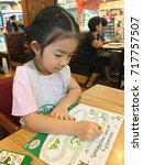 Small photo of Bangkok, Thailand - September 17, 2017 : Little Asian girl is painting with colorful crayon at The Pizza Company. The Pizza Company is famous pizza restaurant in Thailand