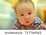 asian baby looking with sceptic ... | Shutterstock . vector #717764563