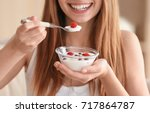 young woman eating yogurt ... | Shutterstock . vector #717864787
