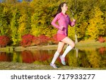 woman running in autumn park ... | Shutterstock . vector #717933277