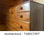 Small photo of Brown wooden tallboy chest of drawers