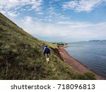 Small photo of A group of tourists walks along the shore along the mountainside.