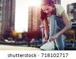 attractive sportswoman tying... | Shutterstock . vector #718102717