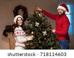young couple in santa hats... | Shutterstock . vector #718114603