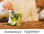 bartender making two mojito... | Shutterstock . vector #718249507