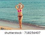 woman in bikini on beach   Shutterstock . vector #718256407