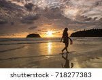 woman walking on the beach at...   Shutterstock . vector #718277383