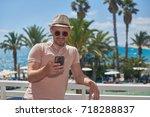 man in sunhat using cellphone...   Shutterstock . vector #718288837