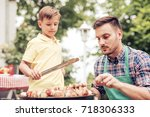 happy father doing barbecue... | Shutterstock . vector #718306333