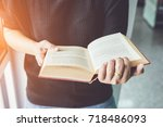 woman holding and reading book... | Shutterstock . vector #718486093