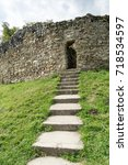 Small photo of Old stone arched door of ruined ancient castle at Cisnadioara fortress in Sibiu, Romania. Stone wall fortress with stairs leading to door. Green grass all around.