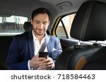 handsome man with phone sitting ...   Shutterstock . vector #718584463