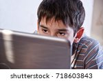 Small photo of Close up of young boy staring at laptop screen during playing computer games, chatting on the Internet or viewing videos.