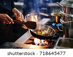 hands of cook frying vegetables ... | Shutterstock . vector #718645477