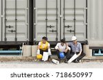 Small photo of Three of engineers are discouraged. Disappointed after unsuccessful work, sitting on floor behind site and hugged their throats.
