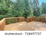 Small photo of Empty upper level deck boasts redwood railings overlooking the lower level deck.