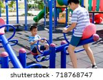 Small photo of Happy Two young asian boy play on the balance bar at outdoor playground under the strong sunlight in summer time.