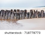 supports of the old wooden pier | Shutterstock . vector #718778773