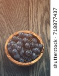 Small photo of ripe isabella grapes in wood bowl on table
