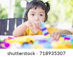 little girl playing with... | Shutterstock . vector #718935307