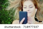 Small photo of Attractive young woman lies on grass, enjoys smartphone. Hair beautifully lie on the lawn.