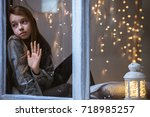 sad child looking out the... | Shutterstock . vector #718985257