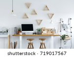 two wooden stools at a desk... | Shutterstock . vector #719017567