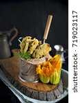 Small photo of zucchini flowers in the grill, with the mazarella and claret. On a black background, on a wooden board
