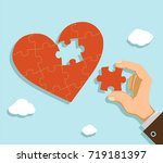 man fold the heart from puzzle... | Shutterstock .eps vector #719181397