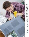 male technician using multimeter | Shutterstock . vector #719186113