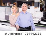 Small photo of Smiling mature couple visit shop with household appliances