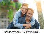man giving piggyback ride to... | Shutterstock . vector #719464303