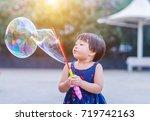 a little girl blowing soap... | Shutterstock . vector #719742163