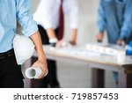 young engineer holding a white... | Shutterstock . vector #719857453