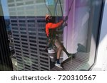 Small photo of Reflection of abseiler abseiling cleaning windows at Sydney building, Australia.