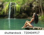Small photo of Happy woman relaxin on a lake with waterfall